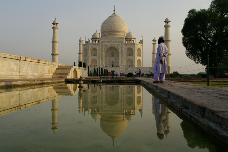 Man reflecting on the Taj Mahal's reflection