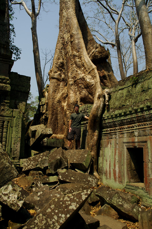 Justin standing on some fallen stones next to a tree on the roof of Ta Prohm in Angkor, Cambodia