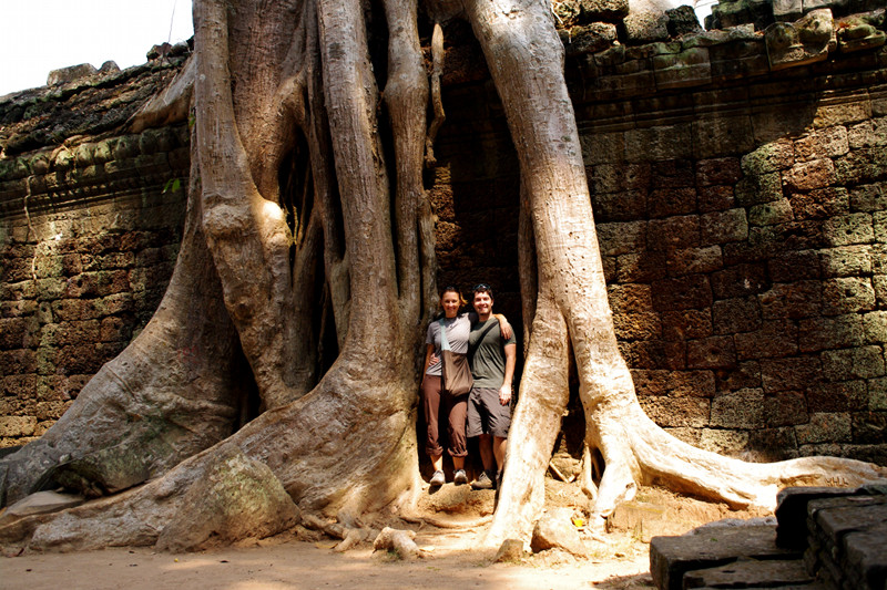 Stephanie and Justin standing between the humongous roots of tree on the wall of Ta Prohm in Angkor, Cambodia