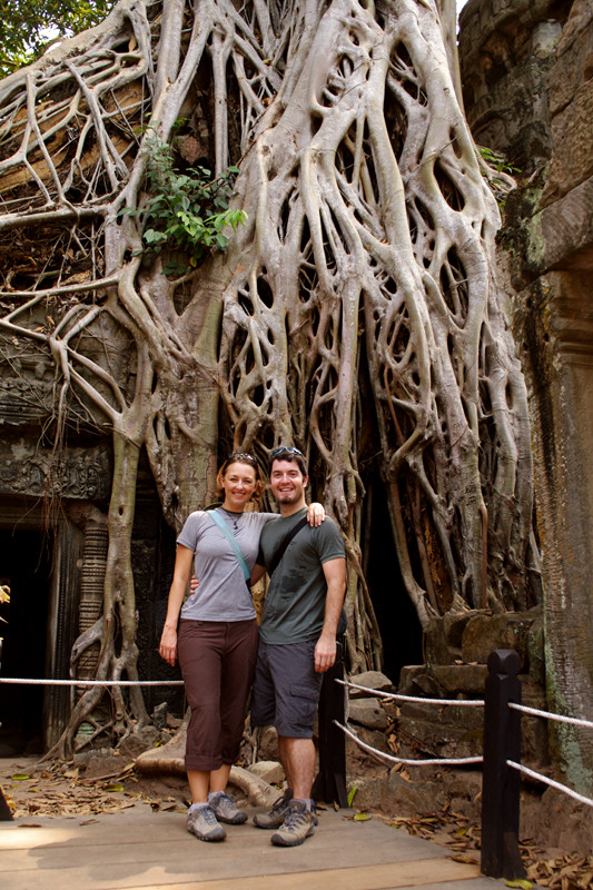 Stephanie and Justin posing on the platform in front of the strangler fig growing on Ta Prohm in Angkor, Cambodia