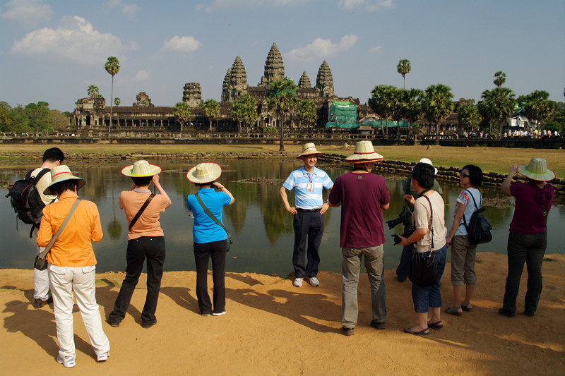 Tourists posing for photos in front of the Angkor Wat reflecting pool