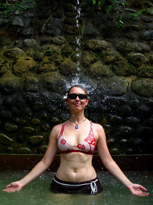 Stephanie meditating under the high waterspout at the Air Panas Banjar hot springs in Bali