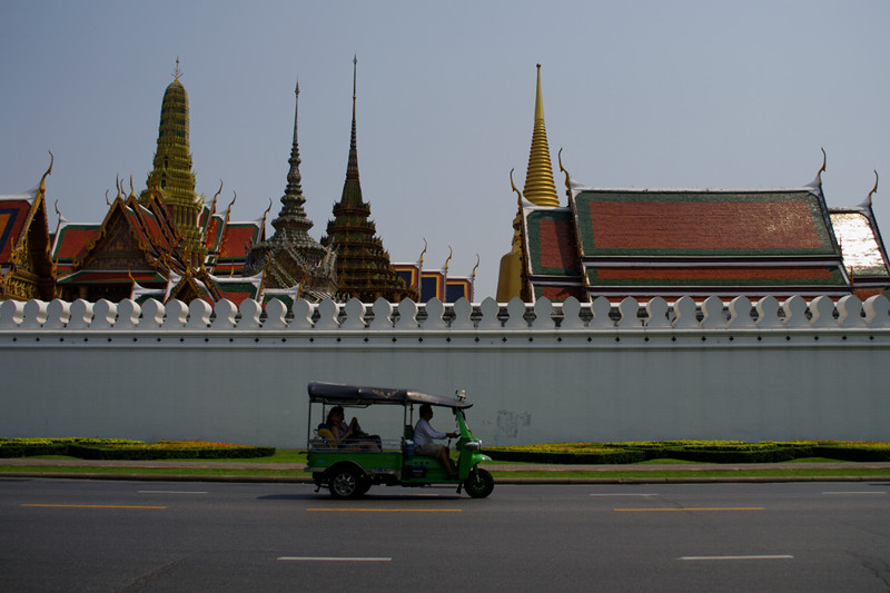 Tuktuk driving by the wall around the Grand Palace in Bangkok, Thailand