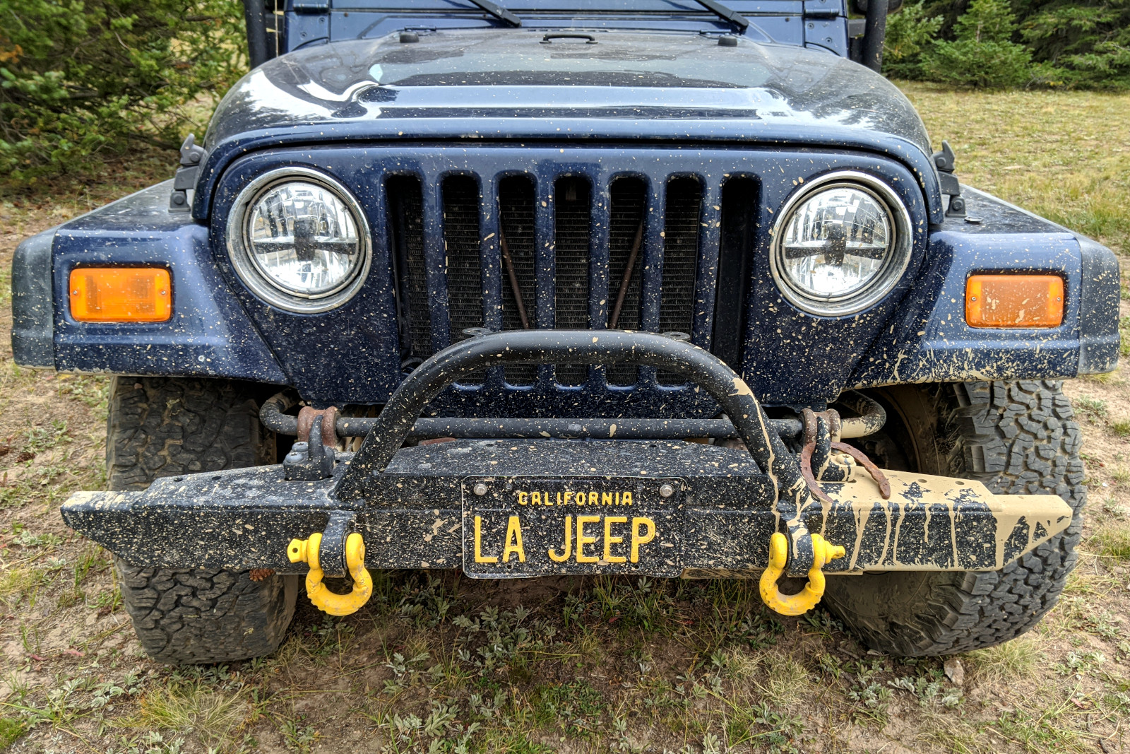 La Jeep's muddy front bumper, plus an old rusty horseshoe