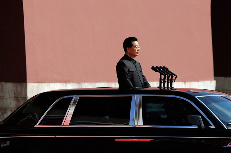Chinese President Hu Jintao standing in a car in front of four microphones
