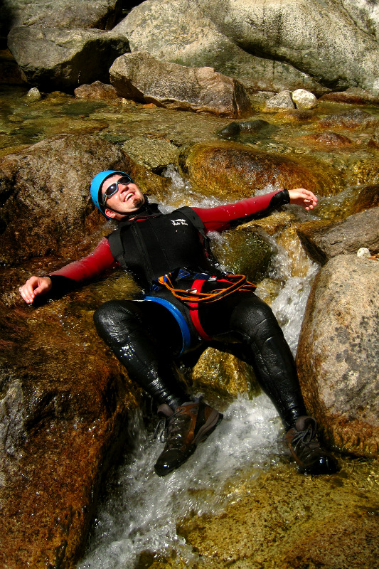 Justin laying in a stream before canyoning (aqua rando) in Corsica