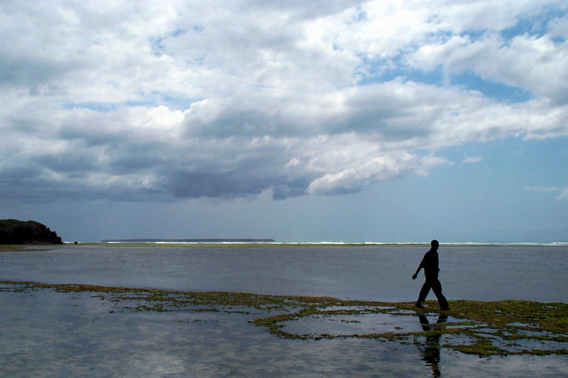 man walking in the indian ocean at low tide