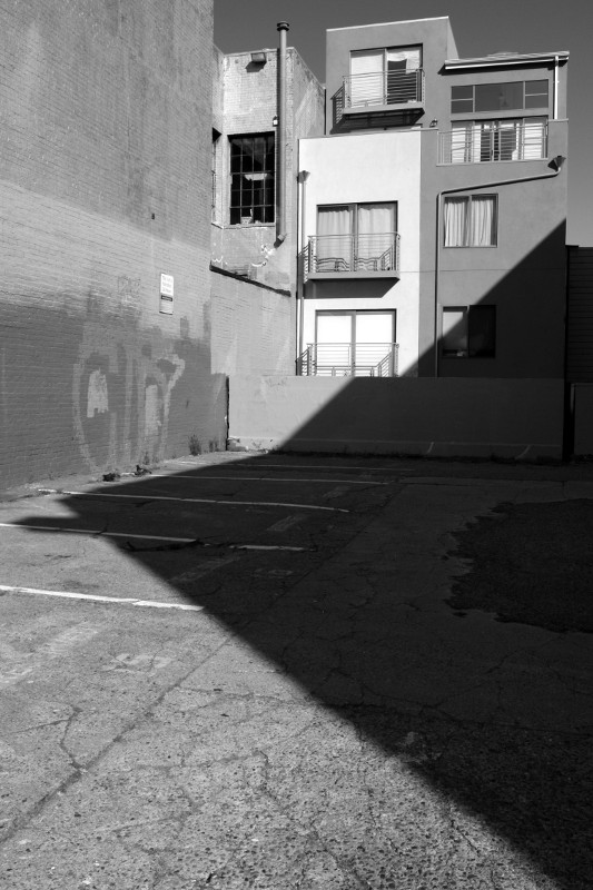 A shadow cuts across an empty lot