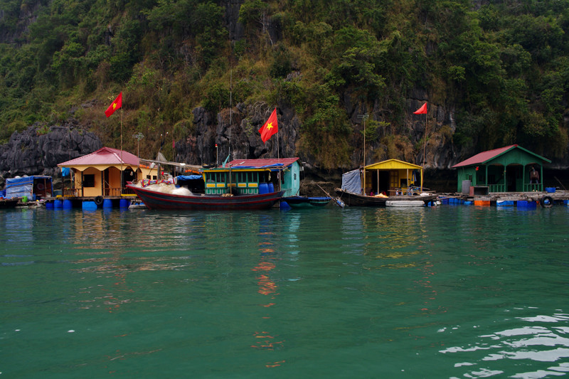 Floating houses in a Hạ Long Bay floating village flying Vietnam flags