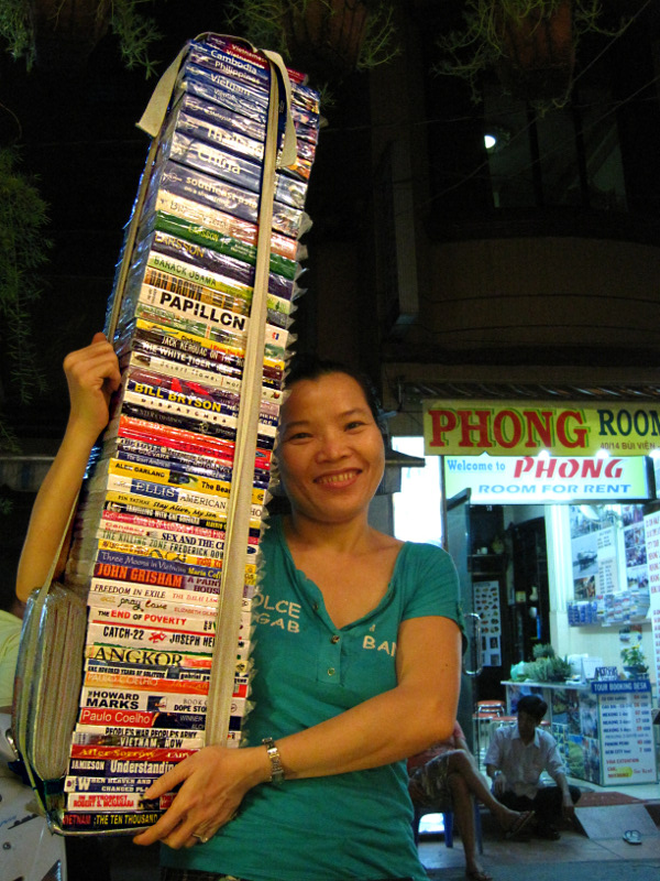 Woman in Ho Chi Minh City (Saigon) with a stack of counterfeit books for sale