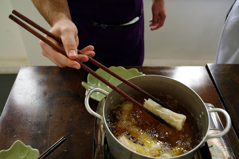 Frying the spring rolls and practicing with large chopsticks