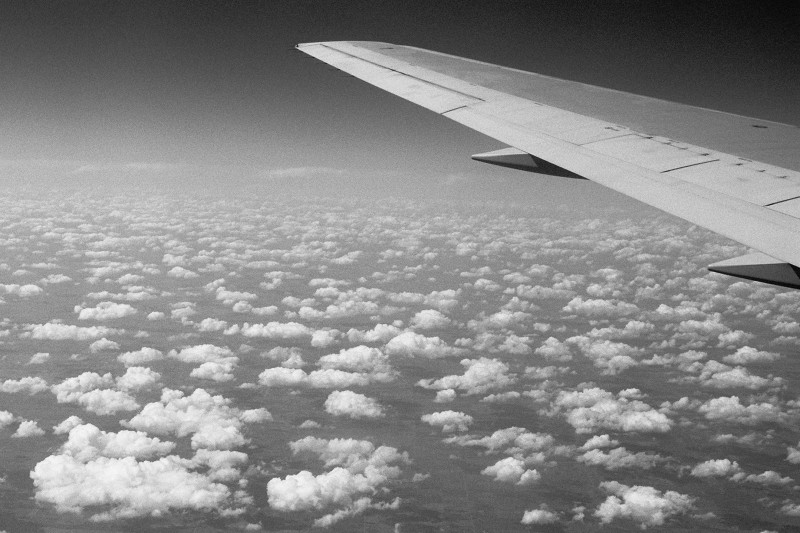 Black and white photo taken in the air above scattered clouds