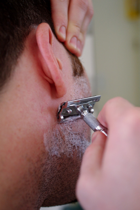 Justin shaving cheek with safety razor