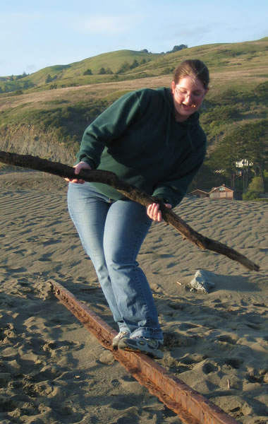 Katie balancing on a railroad track sticking out of a sand dune at Goat Rock Beach