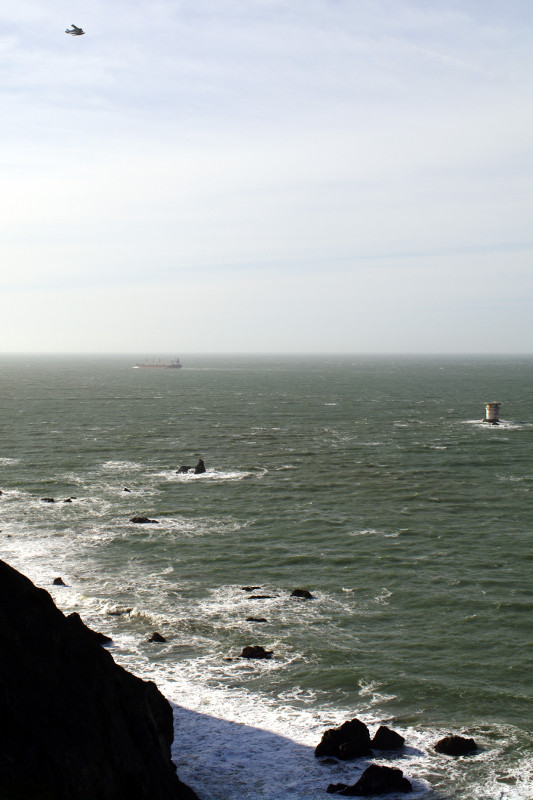 A sea plane, a freighter, and Mile Rock Lighthouse at Land's End, San Francisco