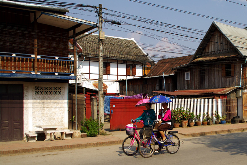 Riding a bicycle with an umbrella in Luang Prabang, Laos