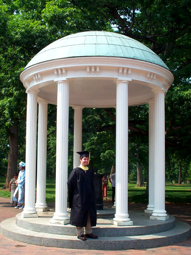 Justin in front of the Old Well with his Masters Graduation gown