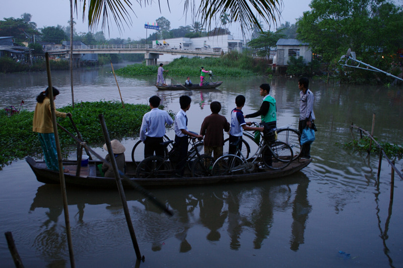 Students with bikes being ferried across the river in the Mekong Delta