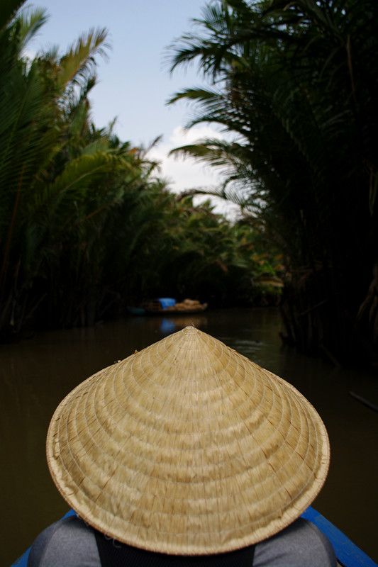 Stephanie wearing a nón lá the conical Asian hat on the small boat to coconut candy factory