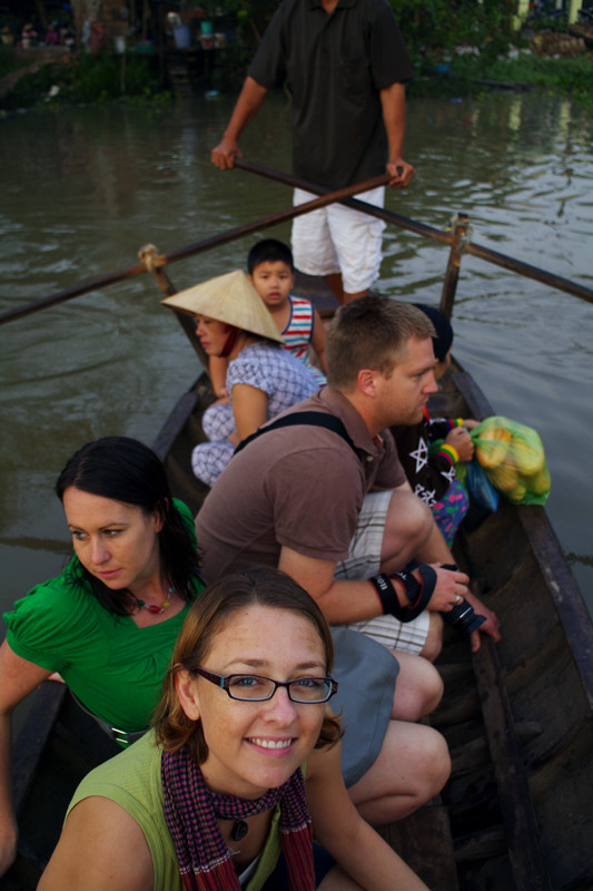 Stephanie squatting on the canoe ferry, crossing a branch of the Mekong Delta