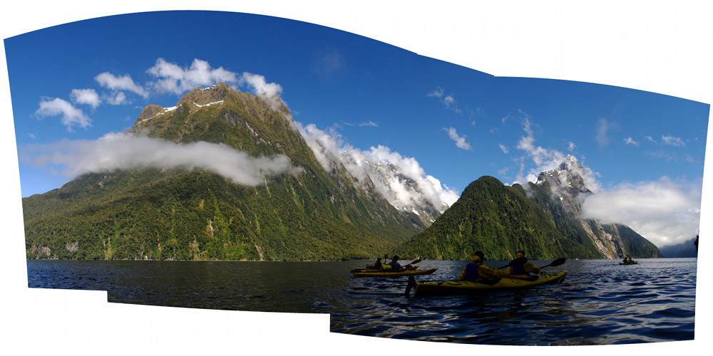 Panorama of Milford Sound kayakers with Mitre Peak enrobed in clouds