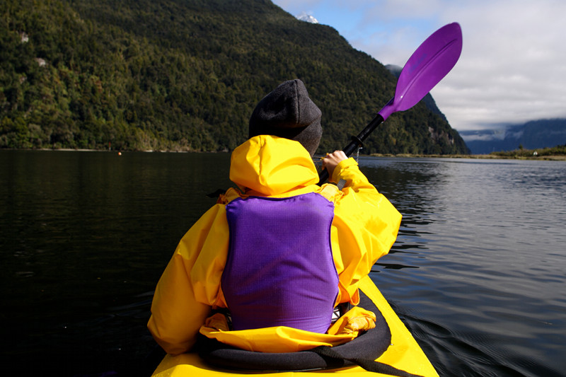 View of Stephanie's back in a tandem kayak while paddling Milford Sound
