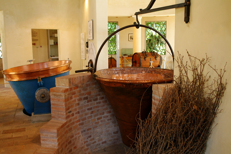 A traditional copper kettle for making Parmesan cheese next to a modern one at the Museo del Parmigiano-Reggiano in Soragna, Italy
