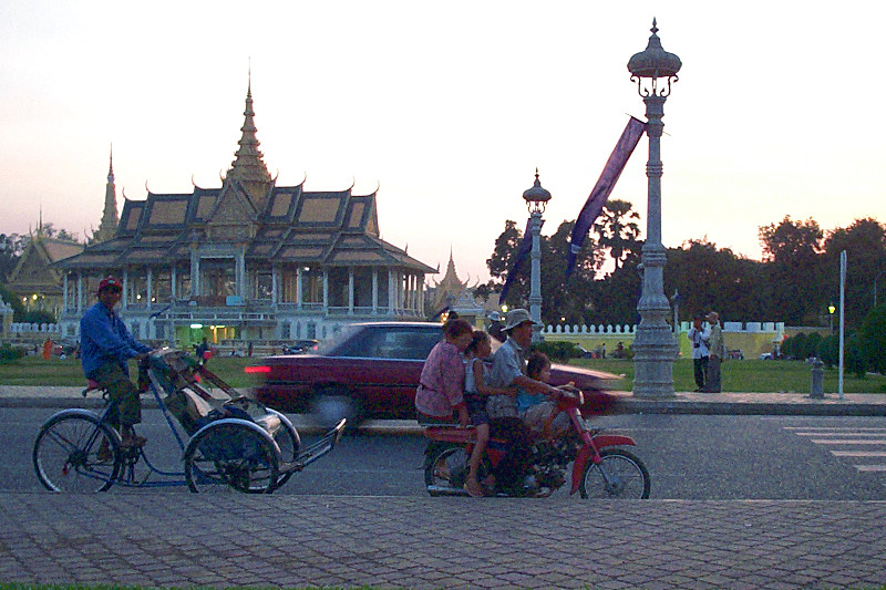 Family of four on a moto in front of the Chan Chhaya Pavilion of the <a href=