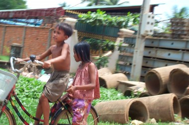 Two children riding a bike (snapped while I was zooming by on the back of a moto)