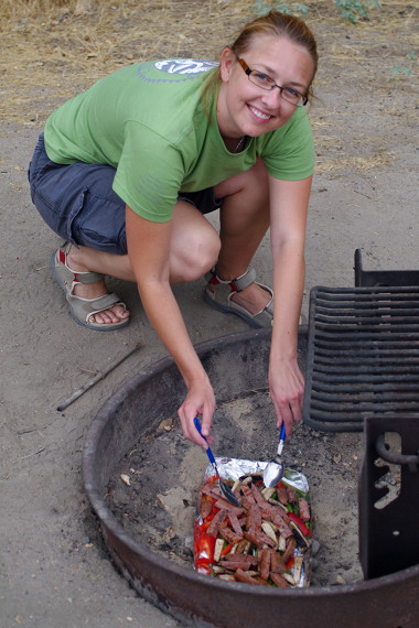 Stephanie cooking over hot coals