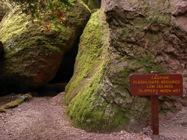 Pinnacles National Monument, sign reads: Caution, flashlights required, low ceilings, slippery when wet