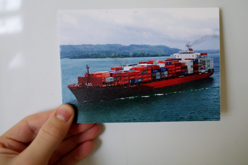 Postful container ship postcard in hand