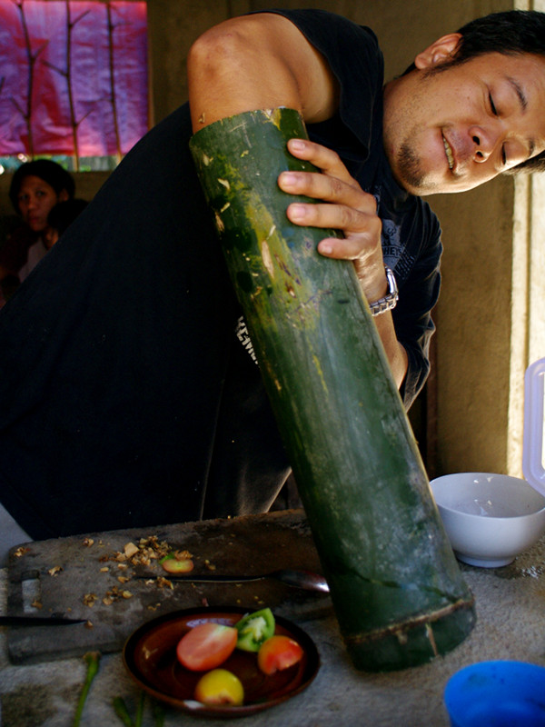 Jeoffrey stuffing a chicken into bamboo for binakol na manok