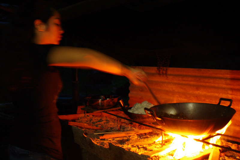 Fatima stirs the rambit adobo over an open fire