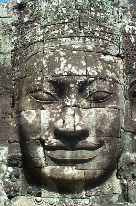 Close up of a smiling Buddha and/or Jayavarman VII face in the Bayon temple at Angkor Thom