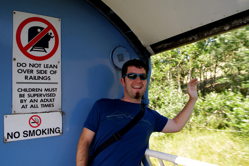 Justin leaning over the side of the railing in the TranzCoastal viewing car