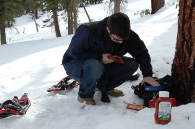 Justin cooking hot dogs in the snow